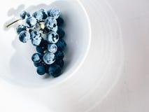 Vid de uva del Merlot en el cuenco blanco de la porcelana en la tabla blanca Imagen de archivo