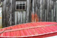 Vid havet - gammal riden ut byggnad bak botten av ett rött målat träfartyg med ett rep arkivfoto