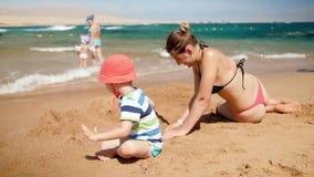 vid?o 4k de peu de gar?on d'enfant en bas ?ge jouant avec sa m?re sur la plage d'ea Famille jouant des jouets et d?tendant des va banque de vidéos