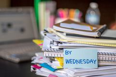 Vid onsdag; Bunt av dokument och bärbara datorn på det funktionsdugliga skrivbordet royaltyfria bilder