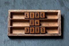 A vida é vida, oposto ao conceito oponente A caixa de madeira gasto, cubos com letras do estilo antigo, pedra cinzenta textured o fotos de stock royalty free