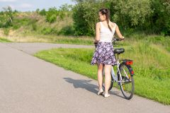 Vida activa Una mujer con una bici disfruta de la visi?n en el bosque del verano foto de archivo