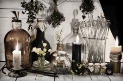 Vida ainda tonificada com garrafas e frascos alquímicos, velas ardentes e ervas curas Fotos de Stock Royalty Free