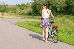 Vida ativa Uma mulher com uma bicicleta aprecia a vista na floresta do ver?o foto de stock