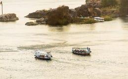 Vida comercial de Nile River por la ciudad de Asuán con los barcos Imagenes de archivo