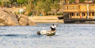 Vida comercial de Nile River por la ciudad de Asuán con los barcos Foto de archivo libre de regalías