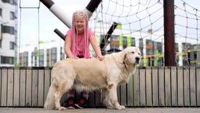 Vida con los animales domésticos en una ciudad moderna - muchacha con un aspecto poco convencional que frota ligeramente su perro almacen de metraje de vídeo