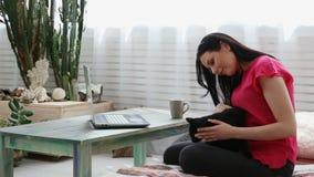 Vida con los animales domésticos la muchacha hermosa está trabajando en casa en un ordenador portátil con un gato negro en sus ma metrajes