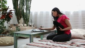 Vida con los animales domésticos la muchacha hermosa está trabajando en casa en un ordenador portátil con un gato negro en sus ma almacen de metraje de vídeo