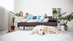 Vida de animales domésticos nacionales en la familia la madre lee el libro a los niños el golden retriever miente en el piso almacen de video