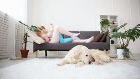 Vida de animales domésticos nacionales en la familia la mamá abraza a sus niños en el sofá en la sala de estar el golden retrieve almacen de metraje de vídeo