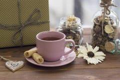 A vida de ano novo ainda com um copo de chá, uns pires, uma caixa de presente e um vidro range com flores Foto de Stock Royalty Free