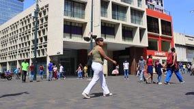 Vida de ciudad: Gente que camina y que hace compras a lo largo de la calle muy transitada en el grande bulevar de Sabana con el e metrajes