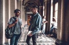 Vida de la universidad Estudiantes jovenes que se colocan en el pasillo de la universidad y hablar con uno a foto de archivo