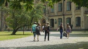 Vida de los estudiantes, hombres jovenes y mujeres caminando en el campus universitario, educación almacen de metraje de vídeo