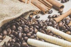 Vida de Stille con los granos de café en saco de la arpillera, palillos de canela y obleas Imágenes de archivo libres de regalías