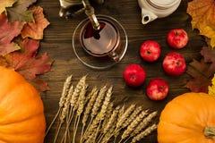 Vida del té todavía c con el samovar, manzanas, calabazas anaranjadas maduras, hojas de arce, trigo en fondo de madera Imagen de archivo libre de regalías