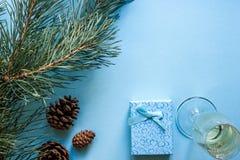 Vida del ` todavía s del Año Nuevo - un vidrio de champán, de decoraciones de la Navidad y de ramas spruce en fondo azul Imágenes de archivo libres de regalías