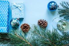 Vida del ` todavía s del Año Nuevo - un vidrio de champán, de decoraciones de la Navidad y de ramas spruce en fondo azul Fotos de archivo
