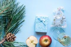 Vida del ` todavía s del Año Nuevo - un vidrio de champán, de decoraciones de la Navidad y de ramas spruce en fondo azul Fotos de archivo libres de regalías