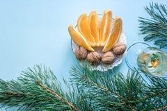 Vida del ` todavía s del Año Nuevo - un vidrio de champán, de decoraciones de la Navidad y de ramas spruce en fondo azul Imagenes de archivo