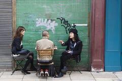 Vida do café da rua Homem na moda no chapéu do vintage que fala com os amigos fora da barra Imagem de Stock Royalty Free