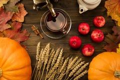 Vida do chá c ainda com samovar, maçãs, abóboras alaranjadas maduras, folhas de bordo, trigo no fundo de madeira Fotografia de Stock