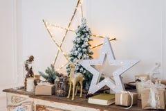 A vida do inverno ainda com decorações do Natal brinca cervos, estrela e caixas de presente no fundo claro foco macio, borrado Foto de Stock