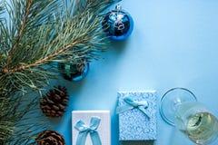 Vida do ` s do ano novo ainda - um vidro do champanhe, das decorações do Natal e de ramos spruce no fundo azul Imagens de Stock
