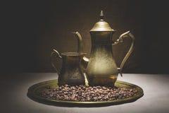 A vida do vintage ainda com o montão de feijões de café aproxima cafeteiras de cobre velhas na bandeja de bronze contra o fundo d Foto de Stock Royalty Free