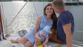 Vida familiar feliz de pares novos com bebê, a mulher de sorriso com bom esposo e a criança no iate da navigação, filme