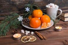 A vida imóvel de ano novo com os mandarino frescos em uma placa, em marshmallows e em canela imagem de stock royalty free