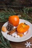 Vida imóvel do Natal com o caqui fresco com cones, canela, marshmallows e mandarino do pinho no fundo de madeira fotografia de stock royalty free