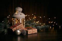 Vida imóvel do Natal com ramos de árvore do abeto, caixa de presente, decorações e lâmpada em um fundo de madeira escuro com a fe fotografia de stock royalty free