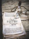Vida imóvel do vintage com imagem do sextante em um livro velho e em uma garrafa de vidro vazia com corda no fundo de madeira env fotografia de stock