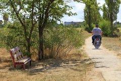 Vida imóvel rural com um banco velho, um residente em um 'trotinette' e uma estrada velha imagens de stock royalty free