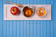 Vida judaica de Rosh Hashana do feriado ainda com mel e maçãs na tabela azul de madeira Vista de acima Imagens de Stock Royalty Free