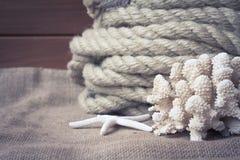 Vida náutica del vintage aún con la cuerda, las estrellas de mar y el coral en viejo fondo de madera Imagen de archivo