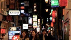 Vida noturno com luzes de néon em restaurantes e em barras traseiros da rua da aleia filme