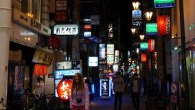 Vida noturno com luzes de néon em restaurantes e em barras traseiros da rua da aleia vídeos de arquivo