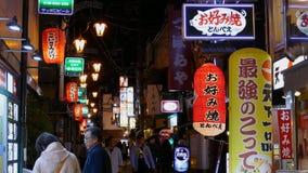 Vida noturno com luzes de néon em restaurantes e em barras traseiros da rua da aleia video estoque