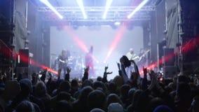 Vida noturno da juventude, multidão de braços de ondulação da juventude acima durante o desempenho do grupo de rock na fase ilumi filme