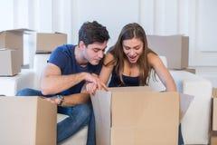 Vida nova Os pares no amor que move-se e mantêm uma caixa em suas mãos e Imagem de Stock Royalty Free