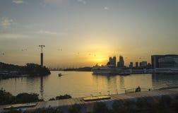 A vida pelos barcos de vela do porto associa as plataformas que bronzeam-se céus azuis dos biquinis do banho de sol claramente um fotos de stock