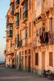 Vida real en la calle durante puesta del sol anaranjada - nadie de La Valeta en la acera foto de archivo