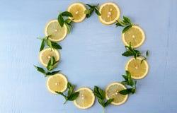 Vida redonda da configuração lisa ainda com hortelã e limão no fundo azul Foto de Stock