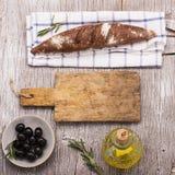 Vida simple de la cocina aún del pan fresco del oscuro-grano, un aceite de oliva del jarro Fotografía de archivo libre de regalías