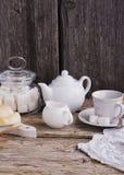 Vida simples da cozinha ainda do chá, do copo, da protuberância do açúcar branco em um banco e de bolos caseiros frescos Fotos de Stock
