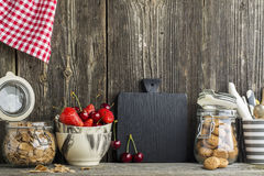 Vida simples da cozinha ainda em um fundo de uma parede de madeira em uma prateleira com cutelaria, as bacias do ferramenta, as d Imagem de Stock Royalty Free