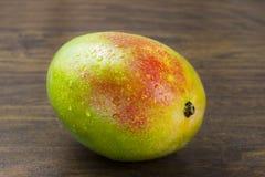 Vida tropical das vitaminas naturais amarelas verdes vermelhas frescas maduras molhadas da manga na madeira Fotos de Stock Royalty Free